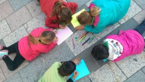 Children preparing a 20N activity in the floor of their village main square.